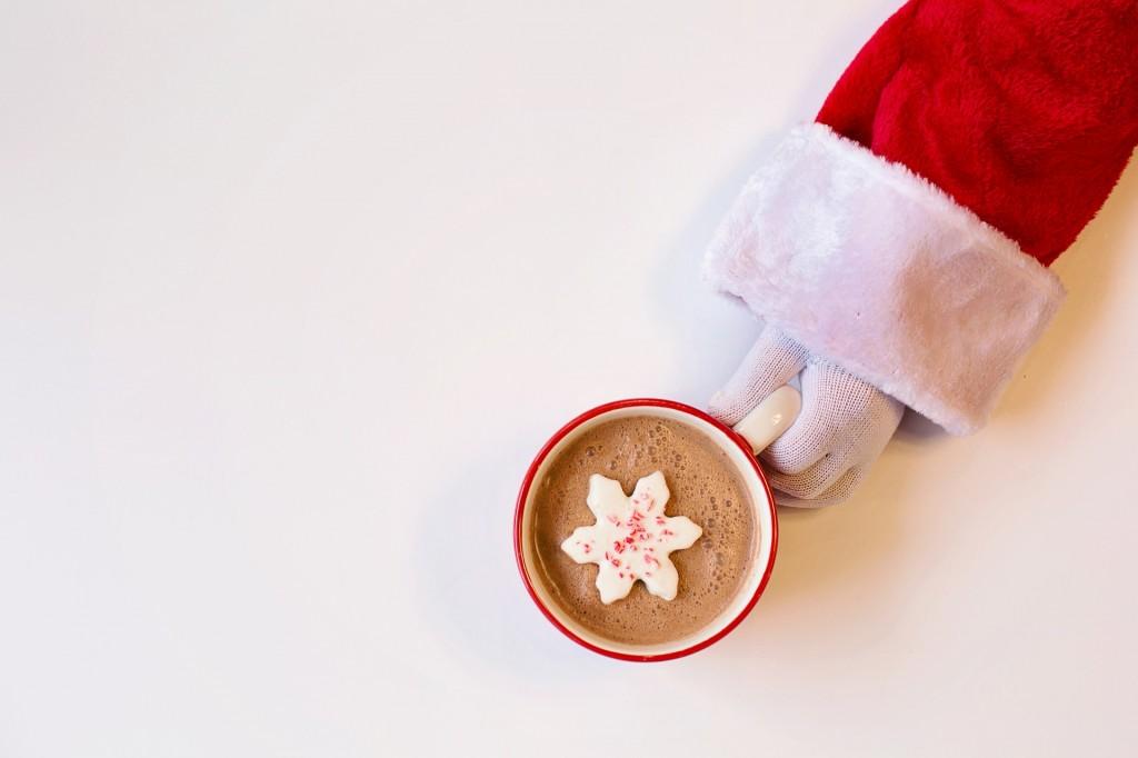 santa's hand holding mug of hot chocolate