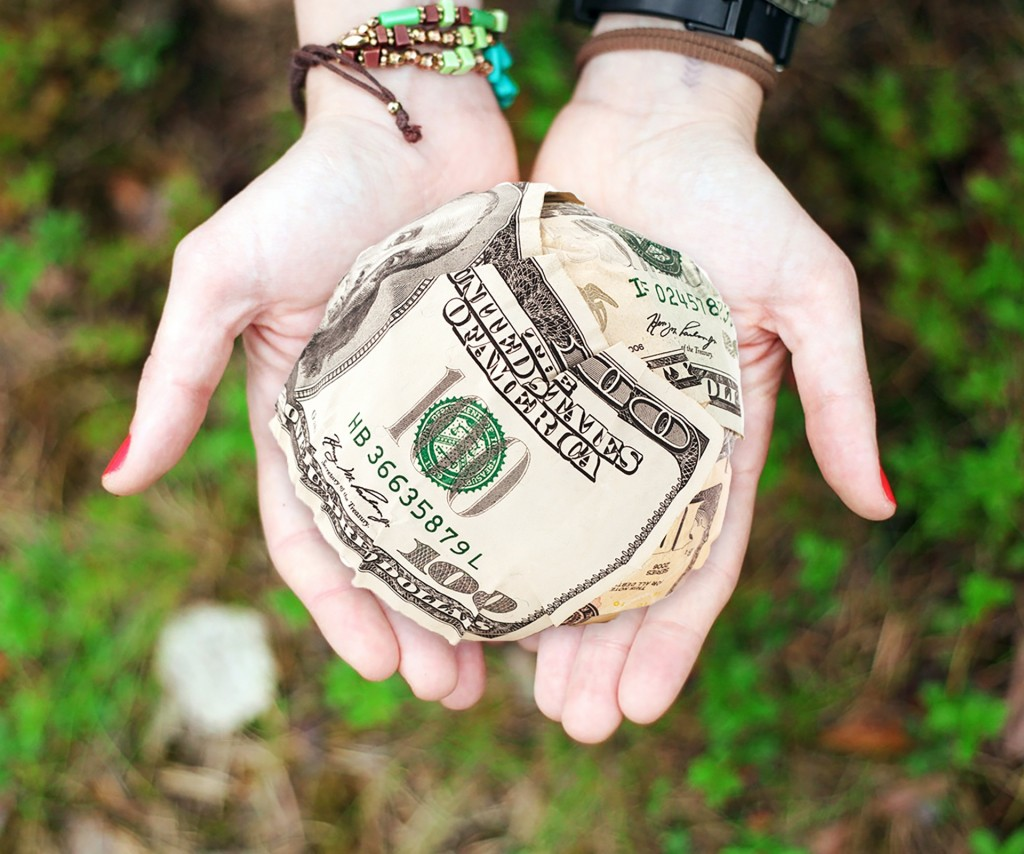 hand holding ball of cash