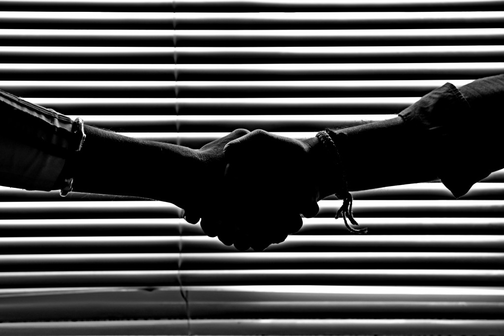 handshake silhouetted by blinds