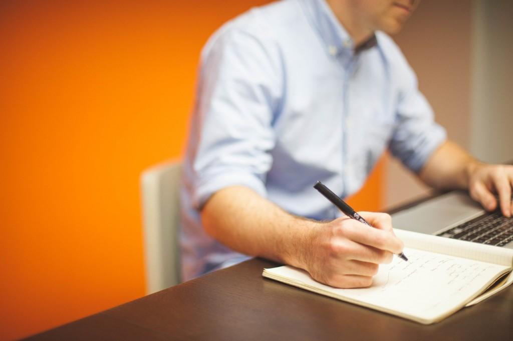 man writing on notebook
