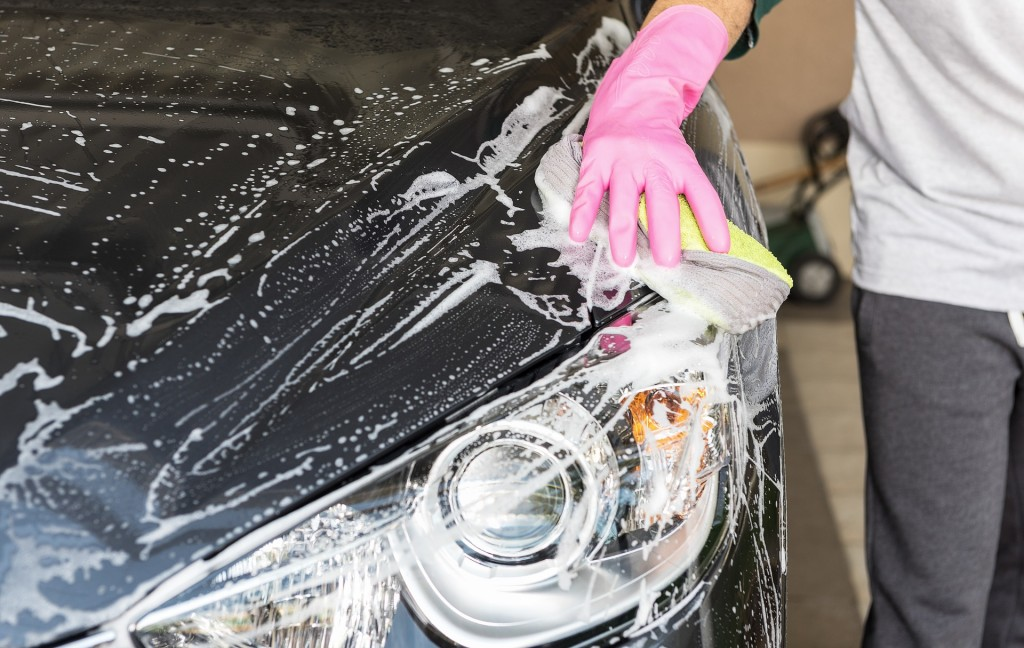 gloved hand washing car