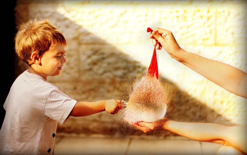 little boy popping a water balloon