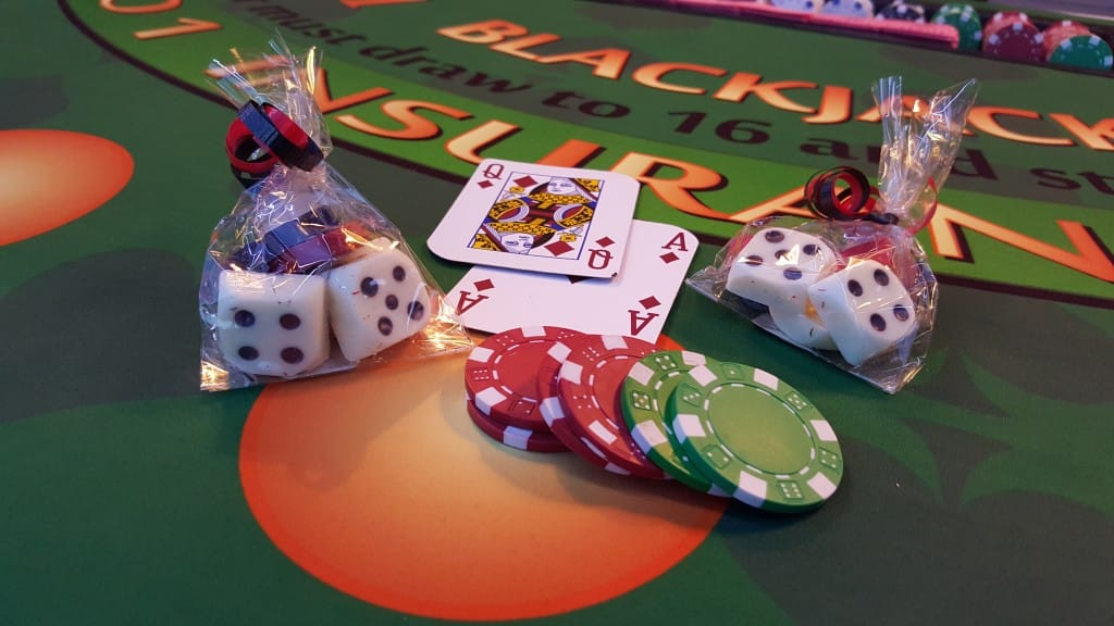 candied dice in gift bag with playing cards and poker chips on black jack table