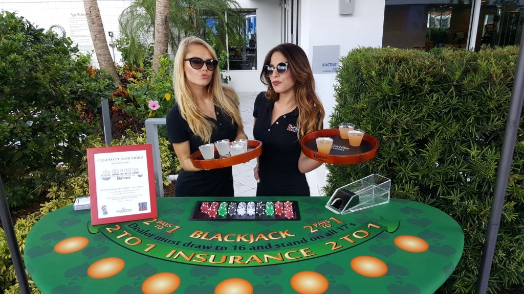 ladies in sunglasses with drink trays standing behind blackjack table at a charity event