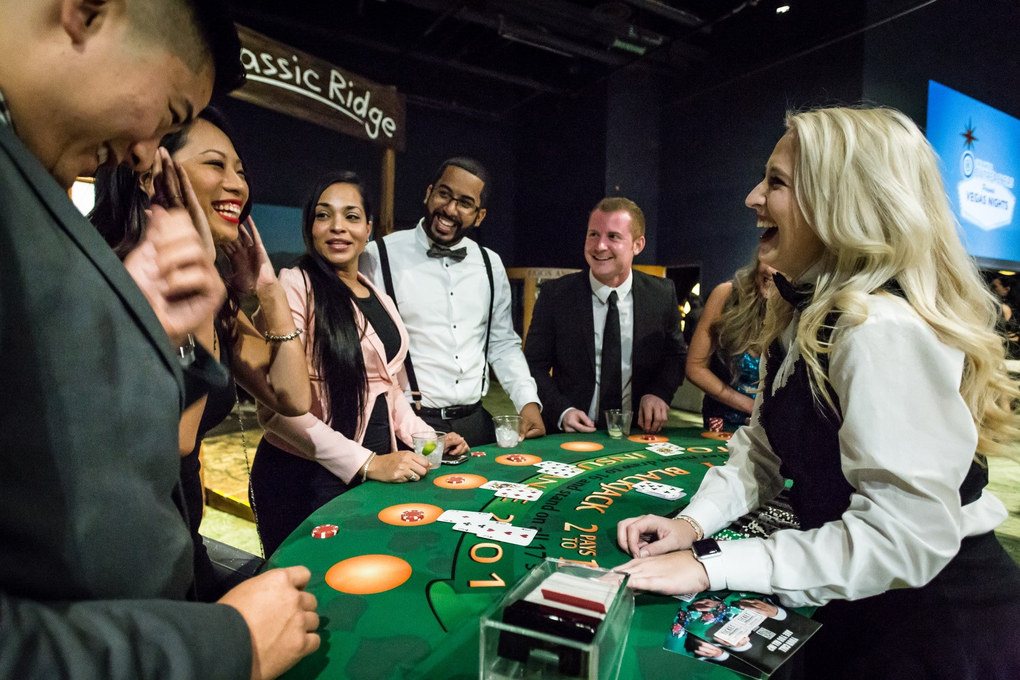 dealer and guests laughing at blackjack table
