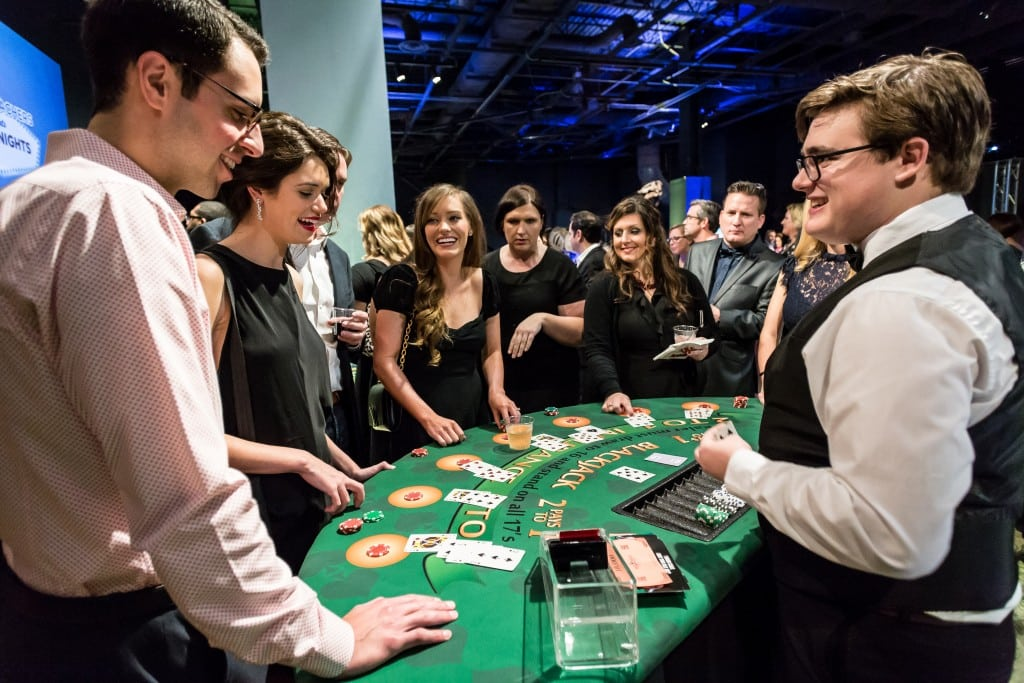 Group of young adults surrounding a black jack table