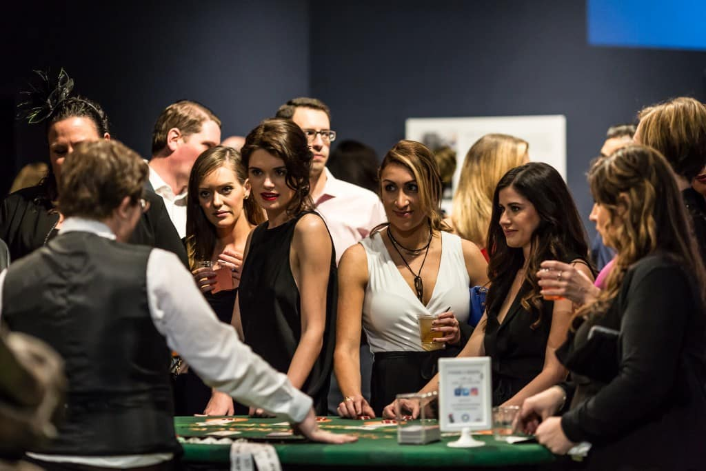 Group of women speaking with black jack card dealer at event
