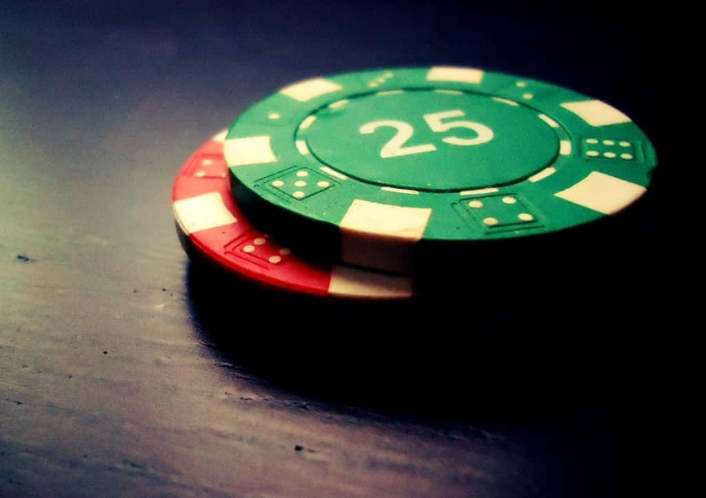 green 25 poker chip stacked on top of red poker chip on wooden table