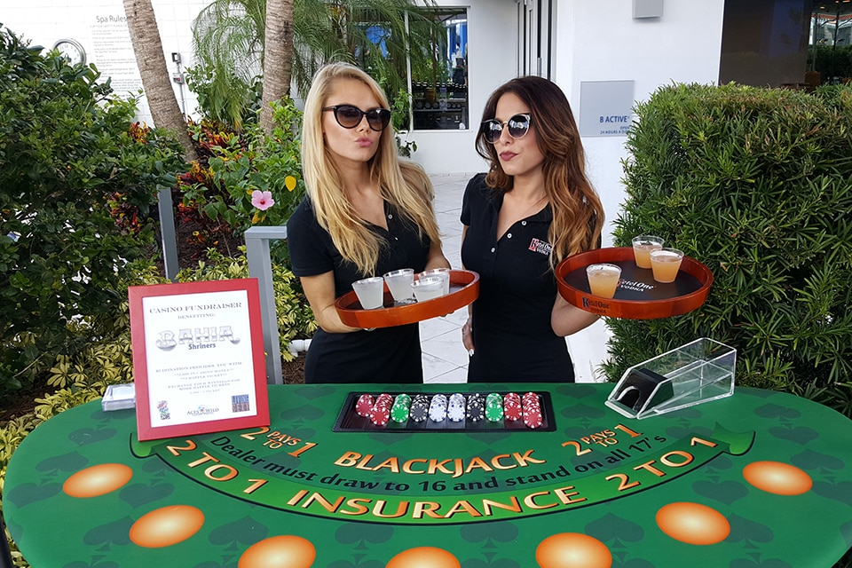 ladies with drink trays standing behind blackjack table at a charity event