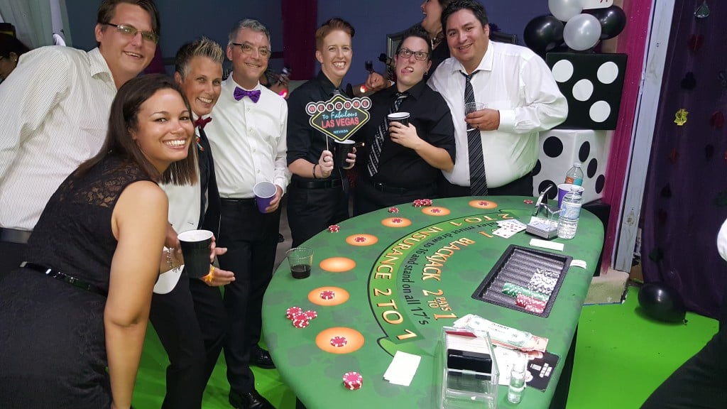 group celebrating with drinks next to blackjack table at Vegas style casino party
