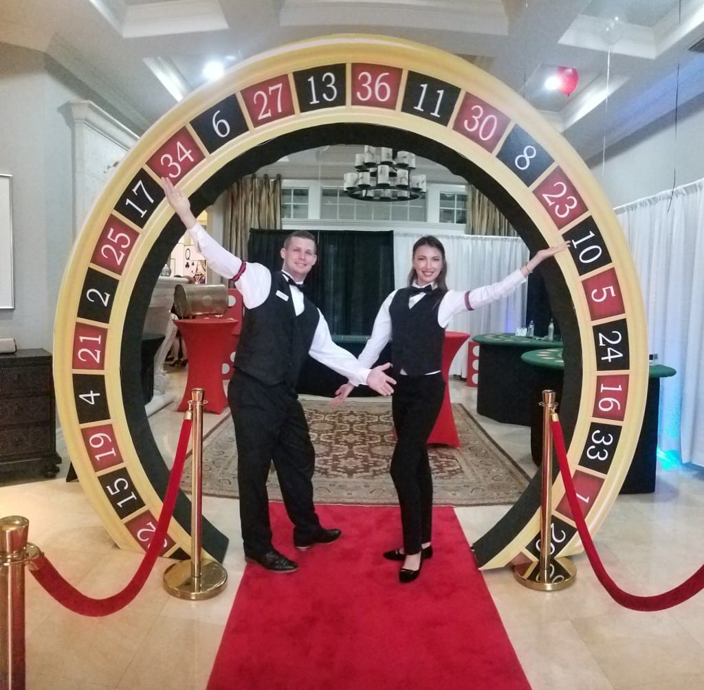 Card dealers standing on red carpet by roulette wheel entry to casino themed party