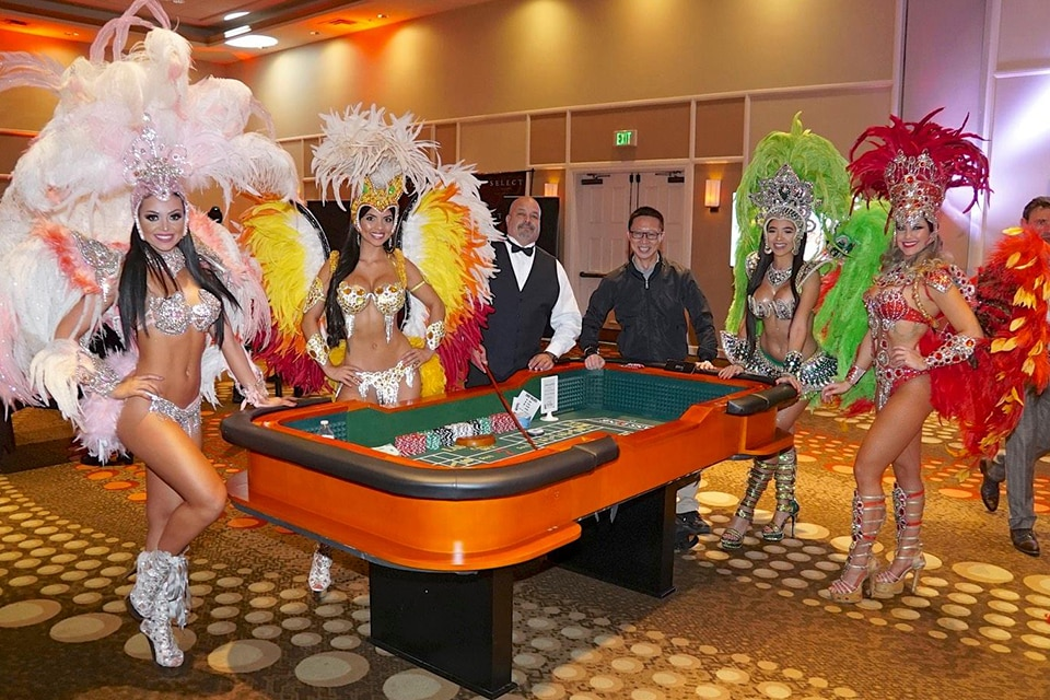 Vegas style show girls standing around craps table with Card Dealer & winner