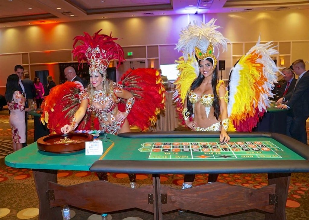 Las Vegas styled and dressed showgirls standing by roulette table at event