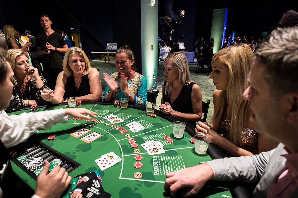 Ladies sitting at black jack table watching cards turn over