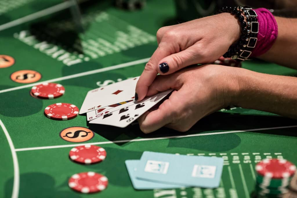 Card player showing card hands at a blackjack table