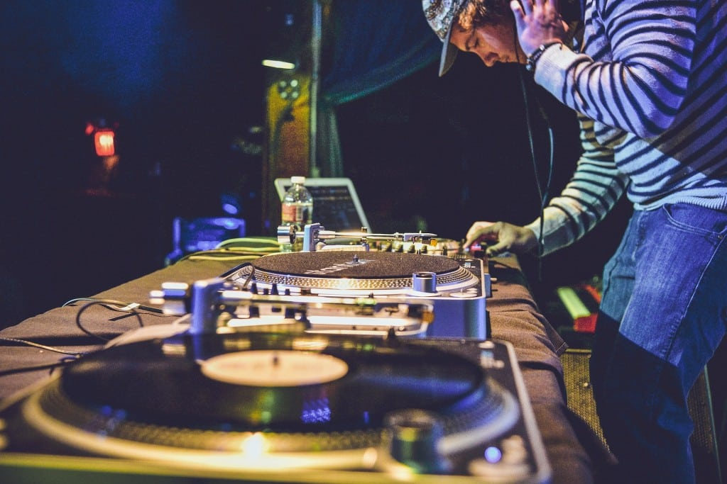 Turntables with DJ playing music at event
