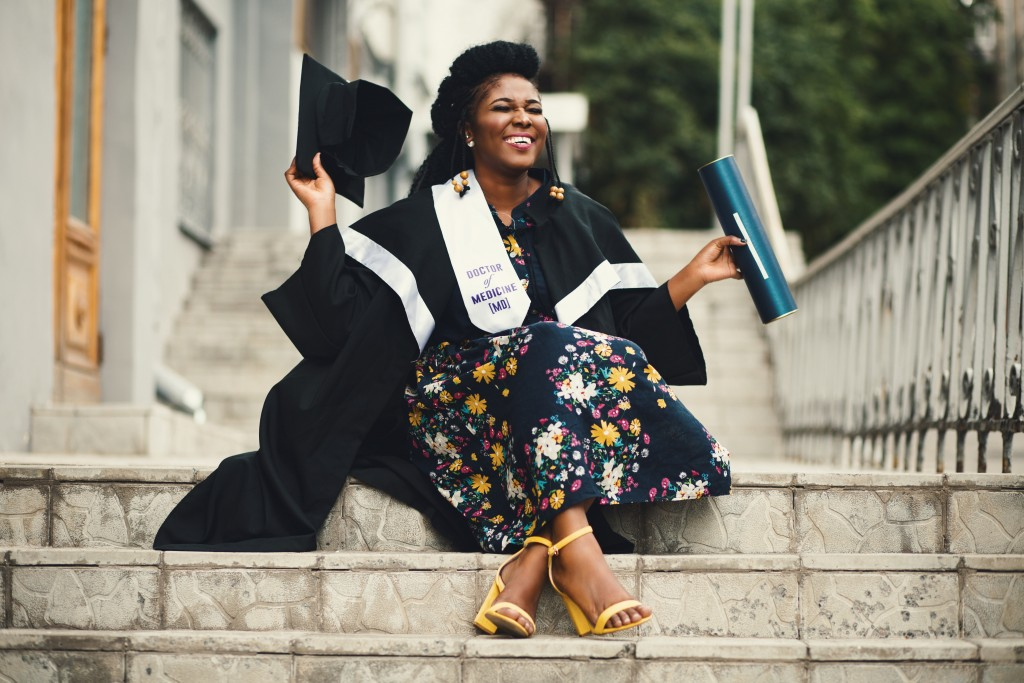 female graduate in cap and gown sitting on steps