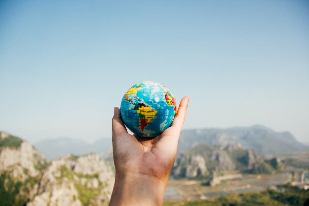 hand holding small globe against desert sky