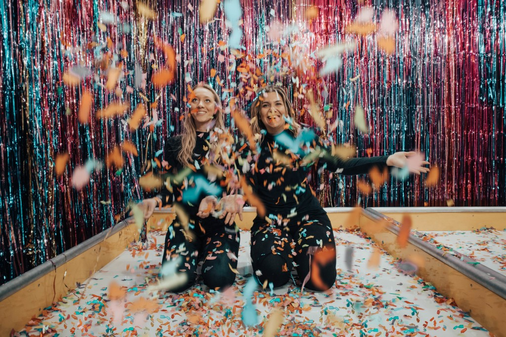two girls throwing confetti in room with metallic streamers