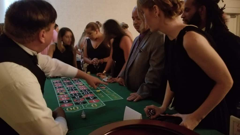 people standing around a roulette table