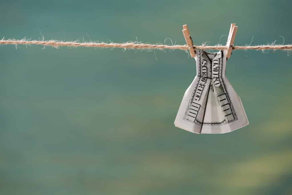 dollar bill folded into dress and hanging on clothesline